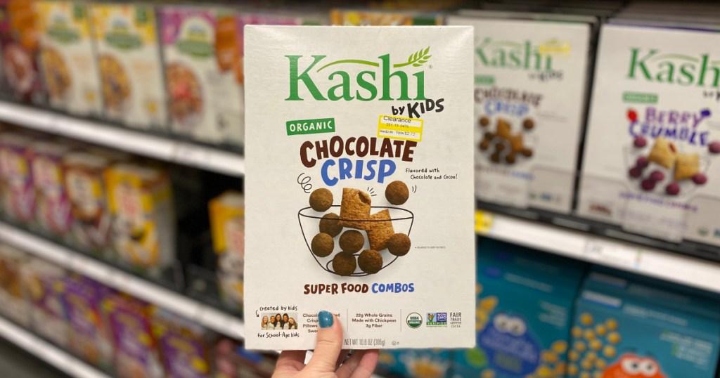 hand holding up box of kids kashi cereal at target