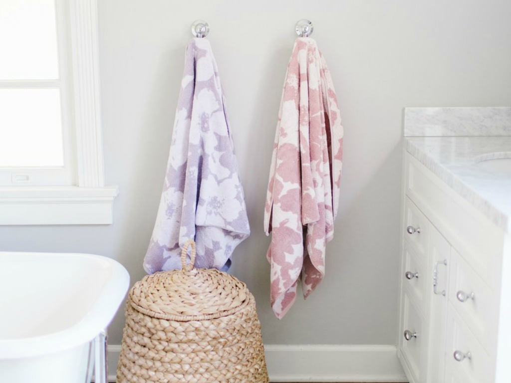 Two floral towels hanging on wall