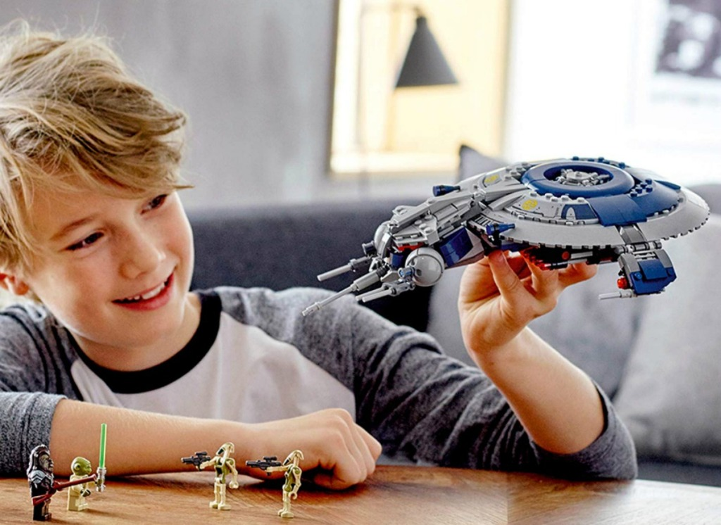 boy playing with LEGO Star Wars set