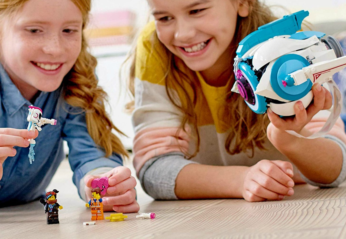 Two girls playing with the LEGO The LEGO Movie 2 Sweet Mayhem's Systar Starship Building Set