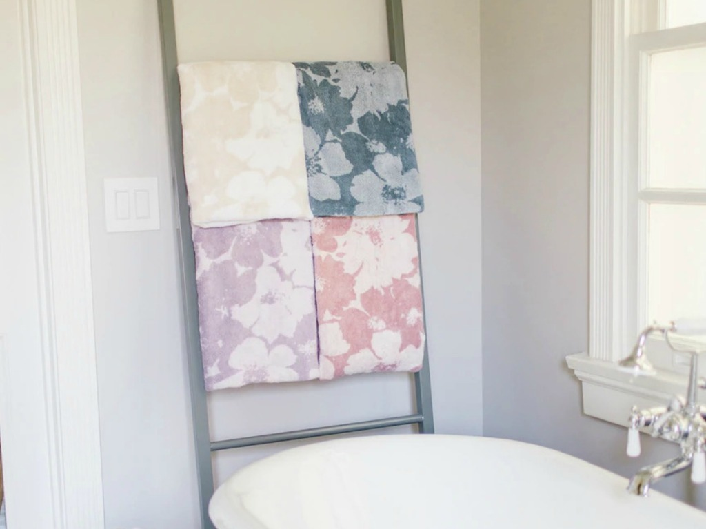 Floral print bath towels in various colors on a towel rack near a bath tub