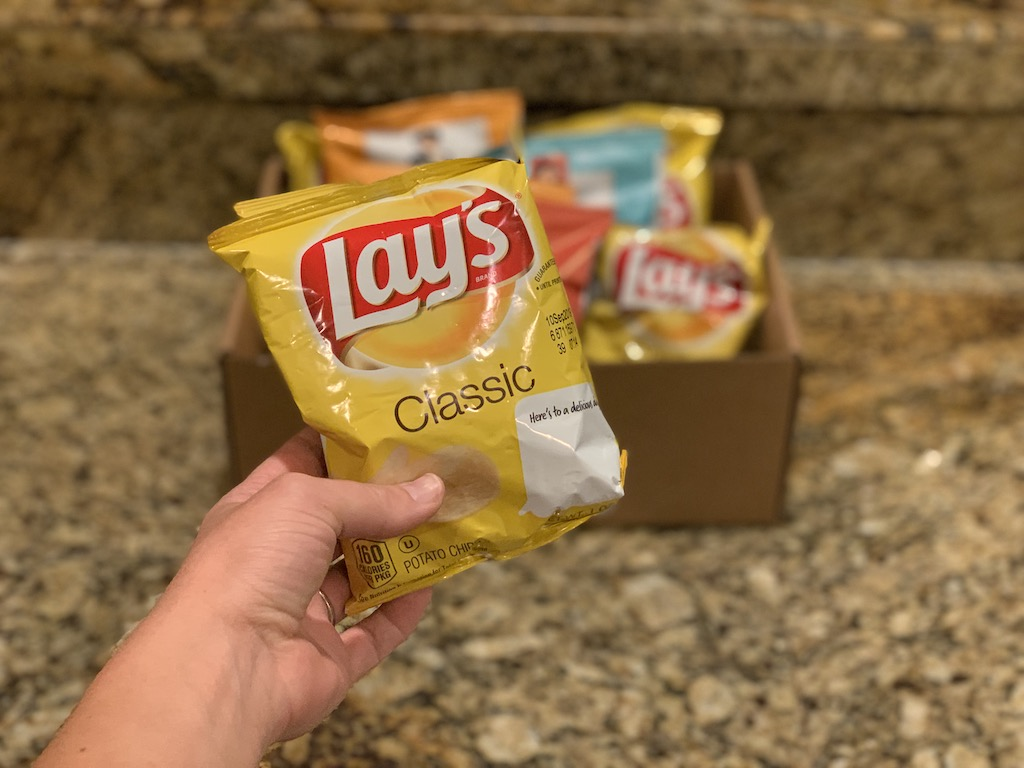 Hand holding up a bag of Lay's Classic Potato Chips