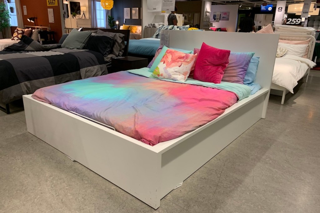 white MALM bed with tye dye comforter in IKEA store