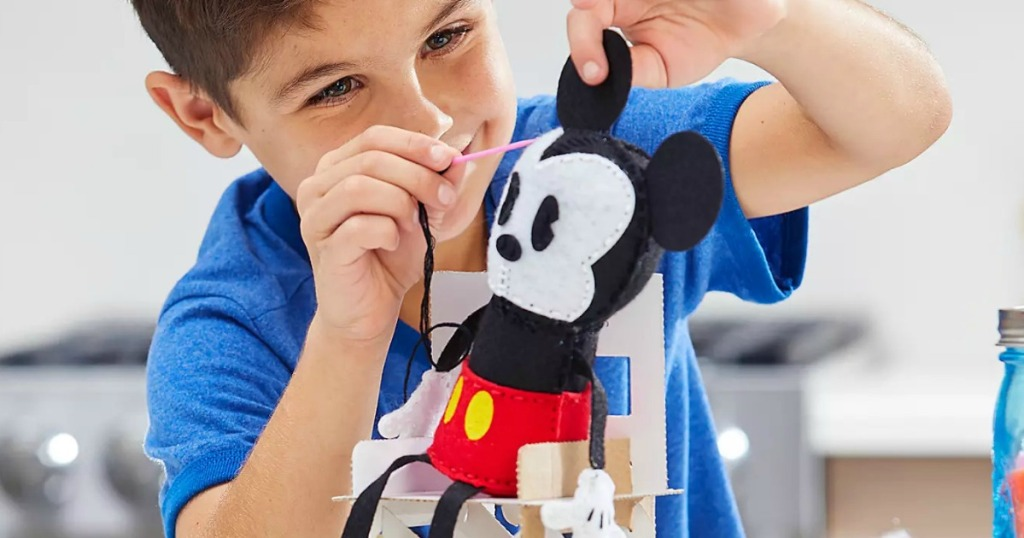 Boy playing with a plush Mickey Mouse