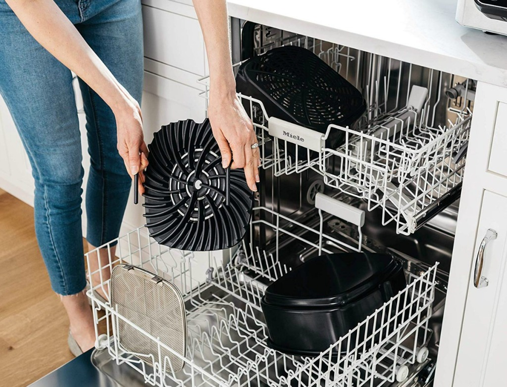 woman putting Ninja Foodi Grill part in a dishwasher