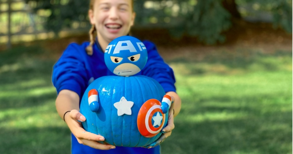 Girl holding No-Carve Pumpkin Kit featuring Captain America