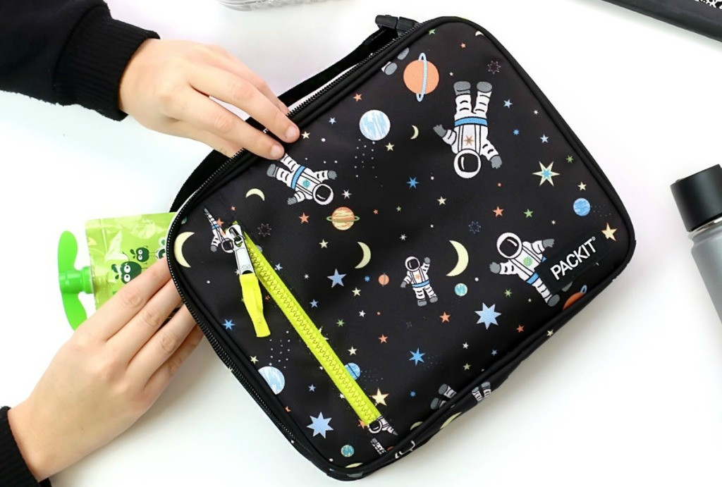 Hands taking applesauce pouch out of Astronaut print lunch bag