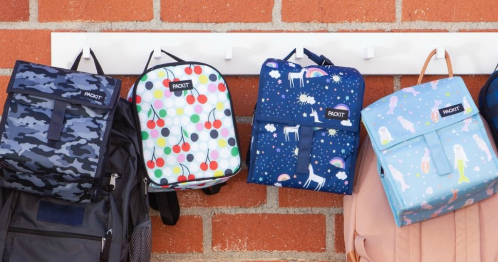 Four styles of freezable lunch bags hung on school wall