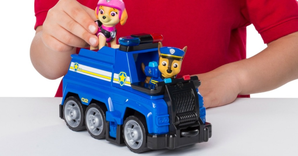 Boy playing with Paw Patrol playset police vehicle and two characters