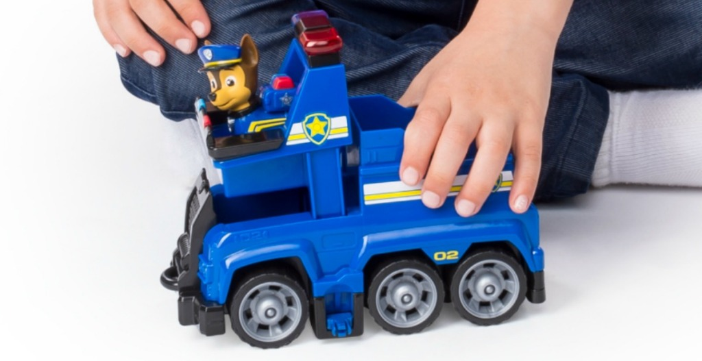 Boy playing with Paw Patrol vehicle playset - police car