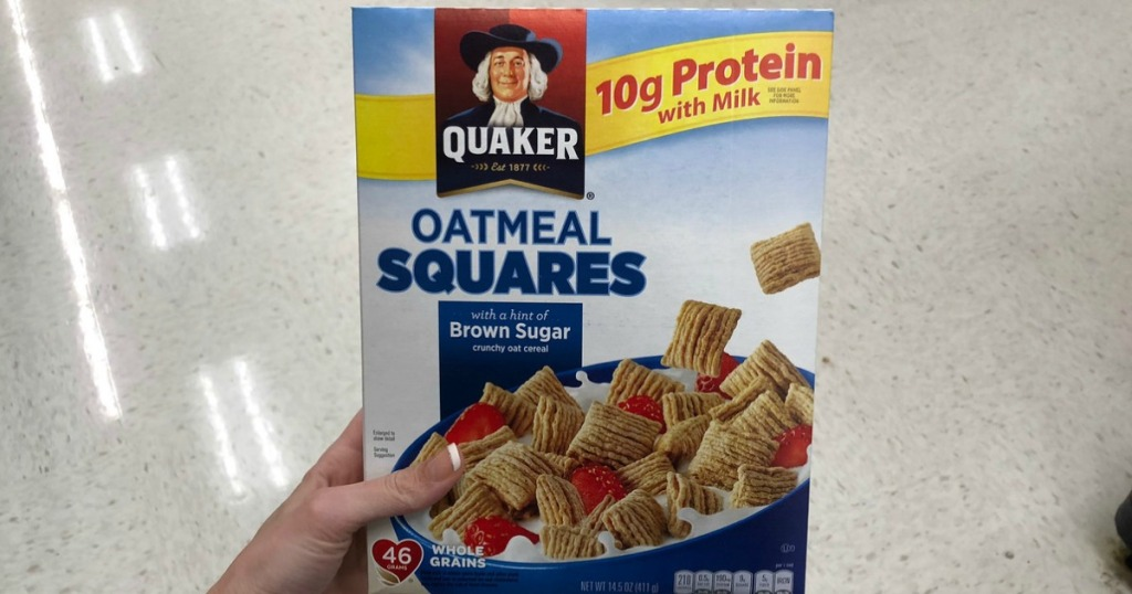 hand holding Quaker Oatmeal Squares in store aisle