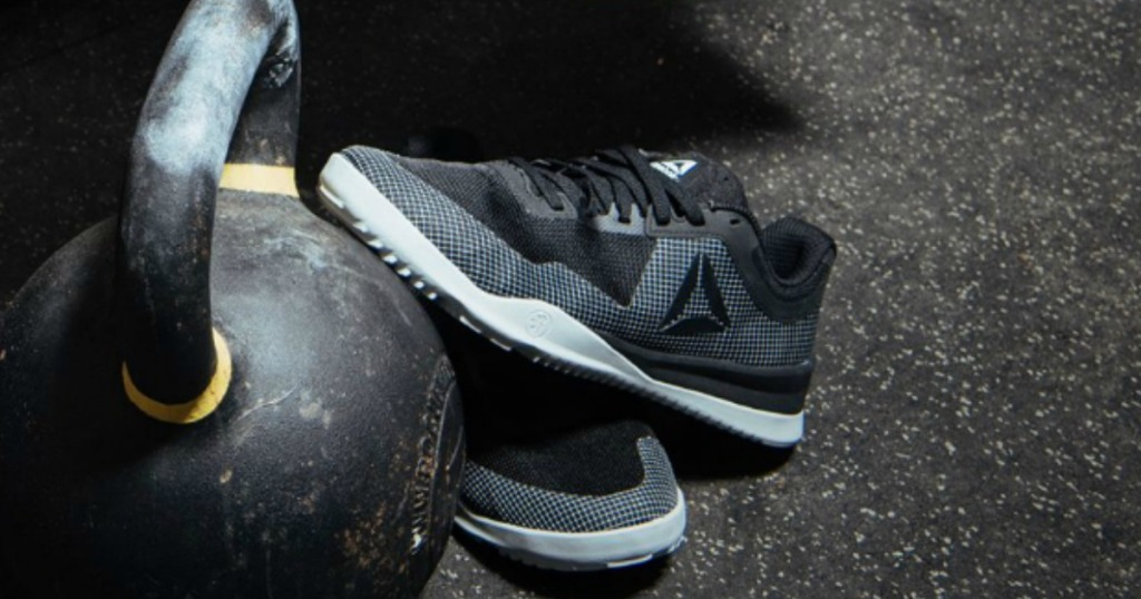 Black and white men's Reebok shoes in gym near kettlebell