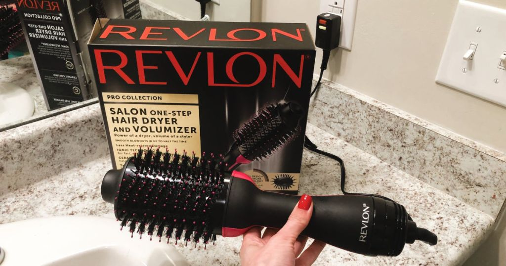 hand holding Revlon Hair Dryer And Volumizer box and dryer on countertop in bathroom