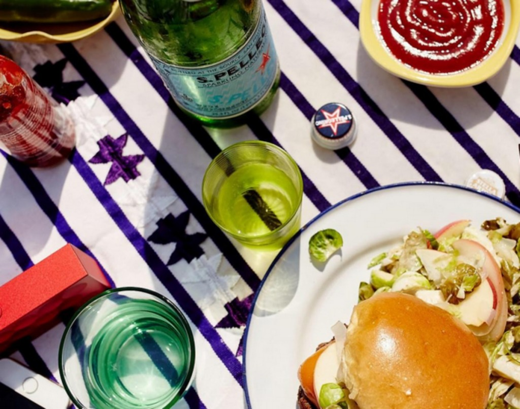 San Pellegrino sparkling water bottle next to a burger and glasses