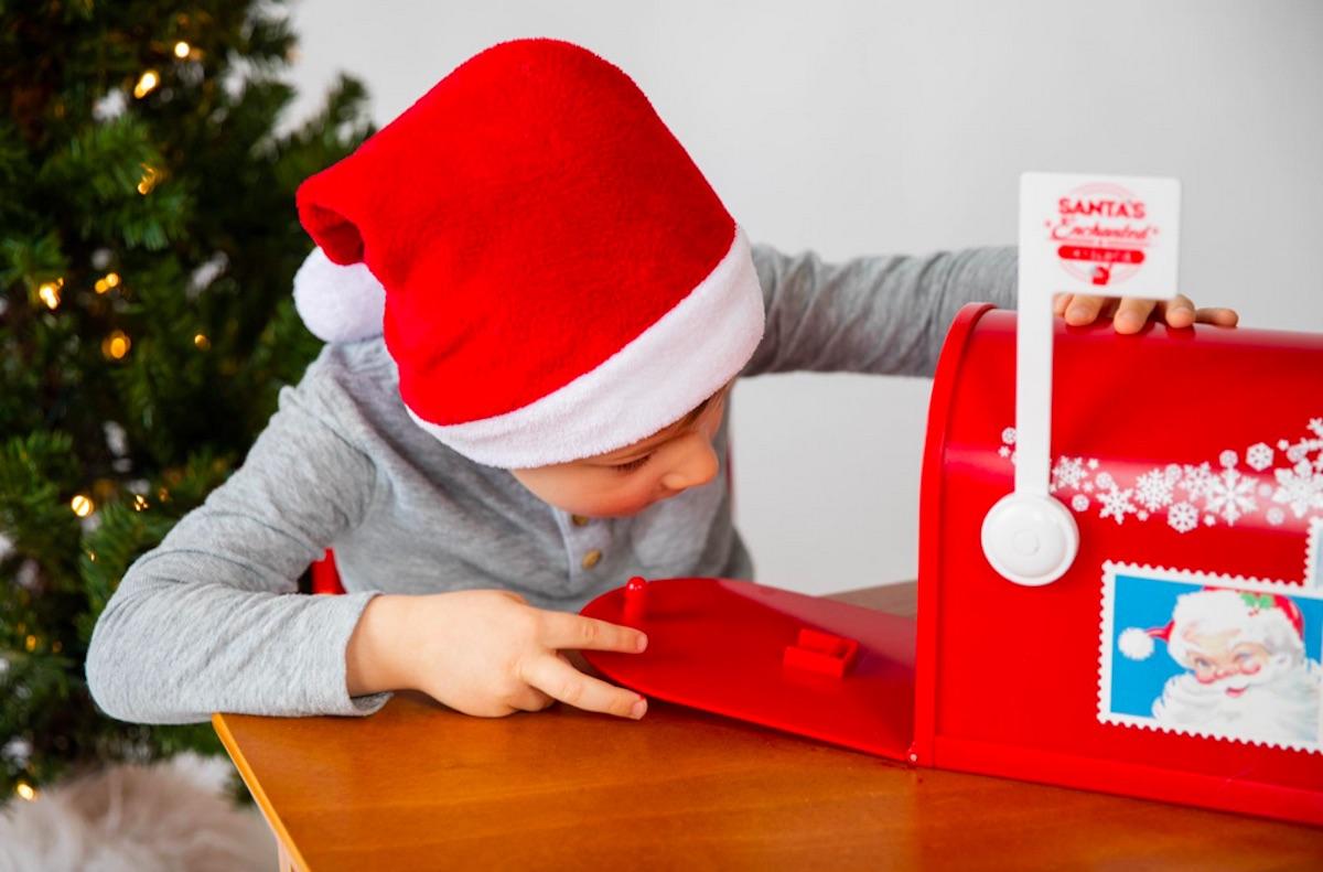 boy placing letter inside Santa's Enchanted Mailbox