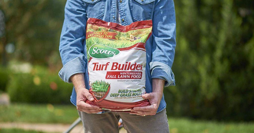 man holding Scotts Turf Builder WinterGuard Fall Lawn Food