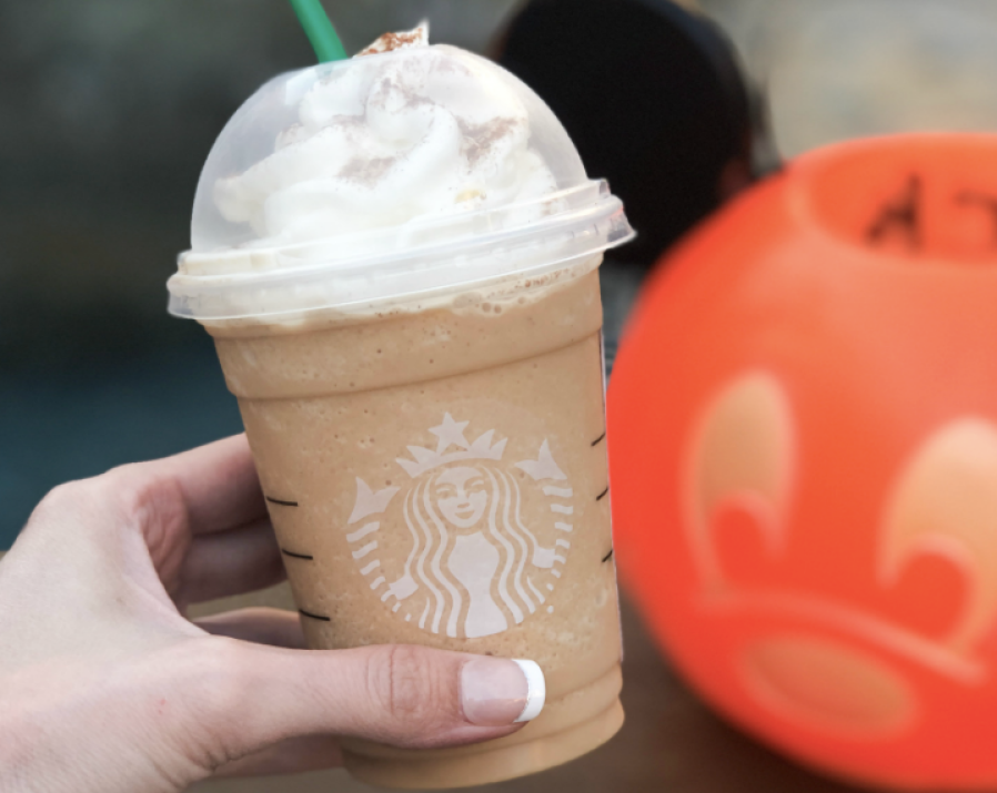 Woman holding Secret Cinderella Drink at Starbucks next to pumpkin