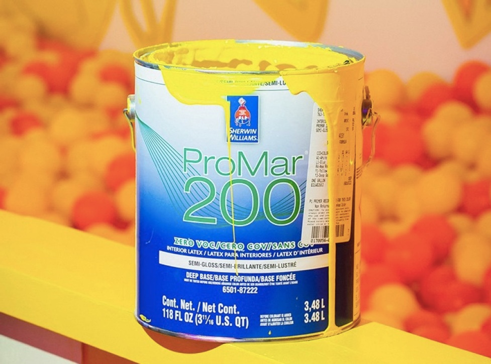 Can of Sherwin Williams paint with yellow paint dripping down sides