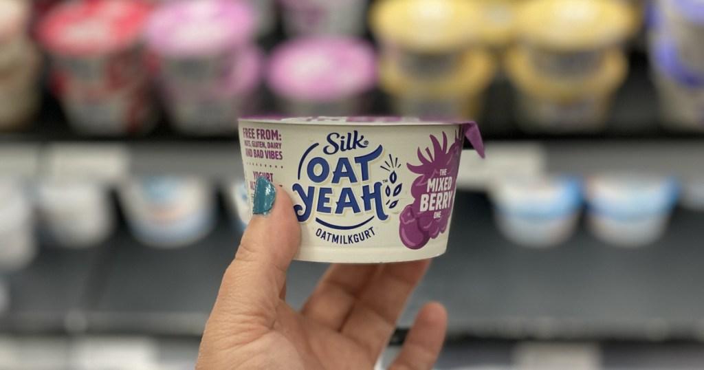 hand holding up silk oat yeah yogurt cup