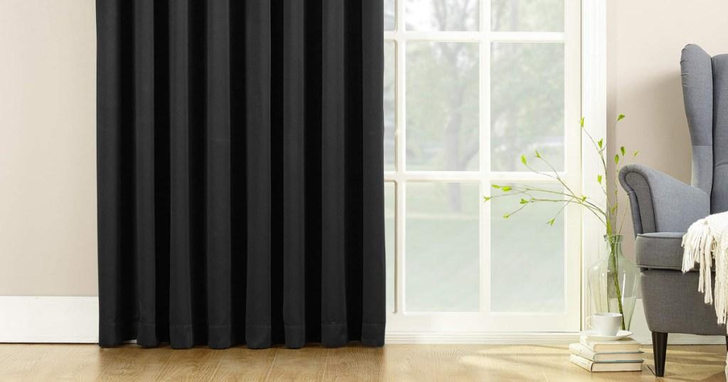 sun zero black curtain panel hanging in living room
