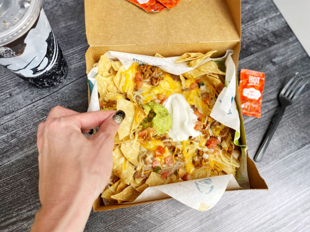 Taco Bell Nacho Box dipping in guacamole