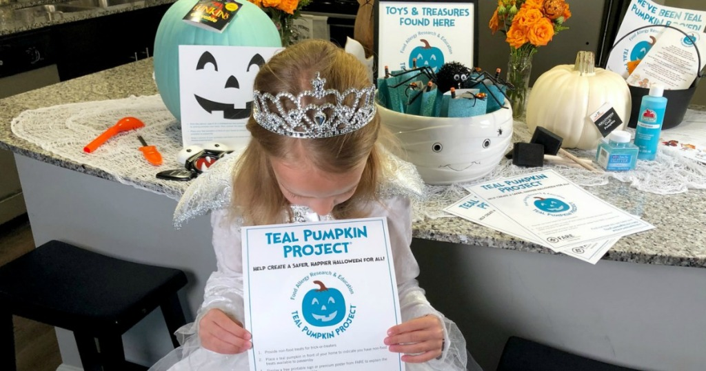 little girl in costume holding teal pumpkin project sign