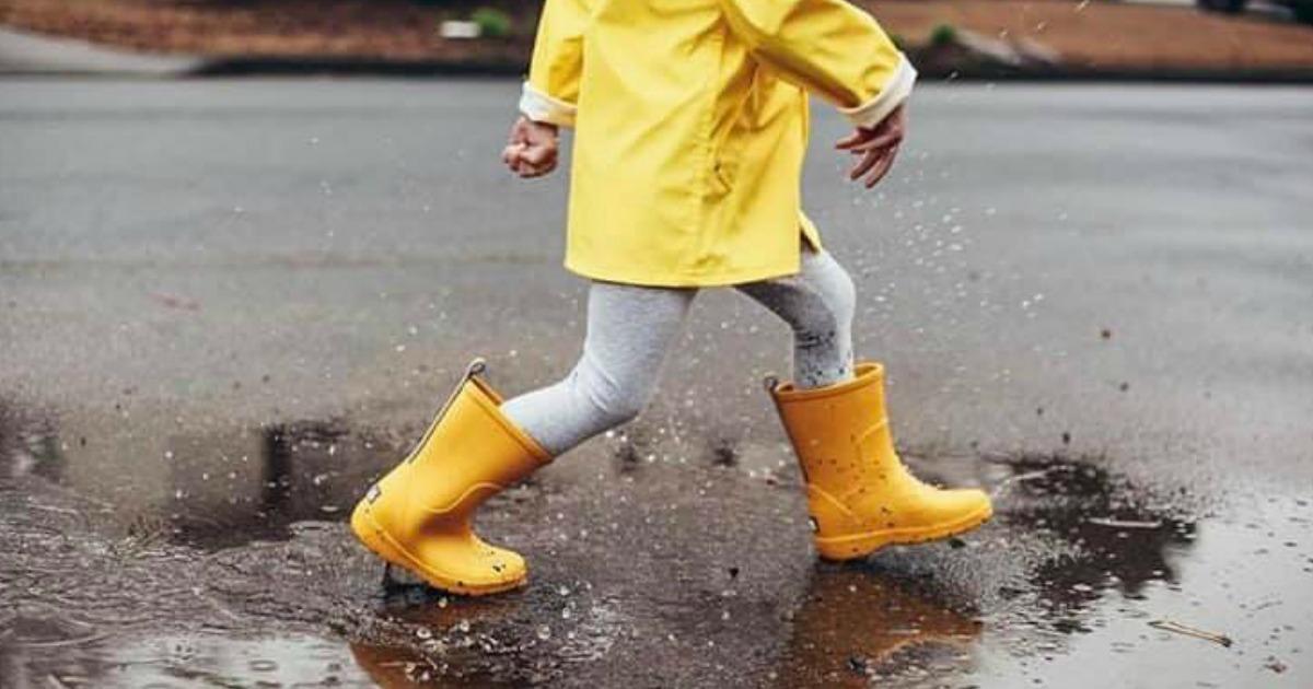 child splashing in puddles wearing yellow Totes Cirrus Charley Kids Rain Boots