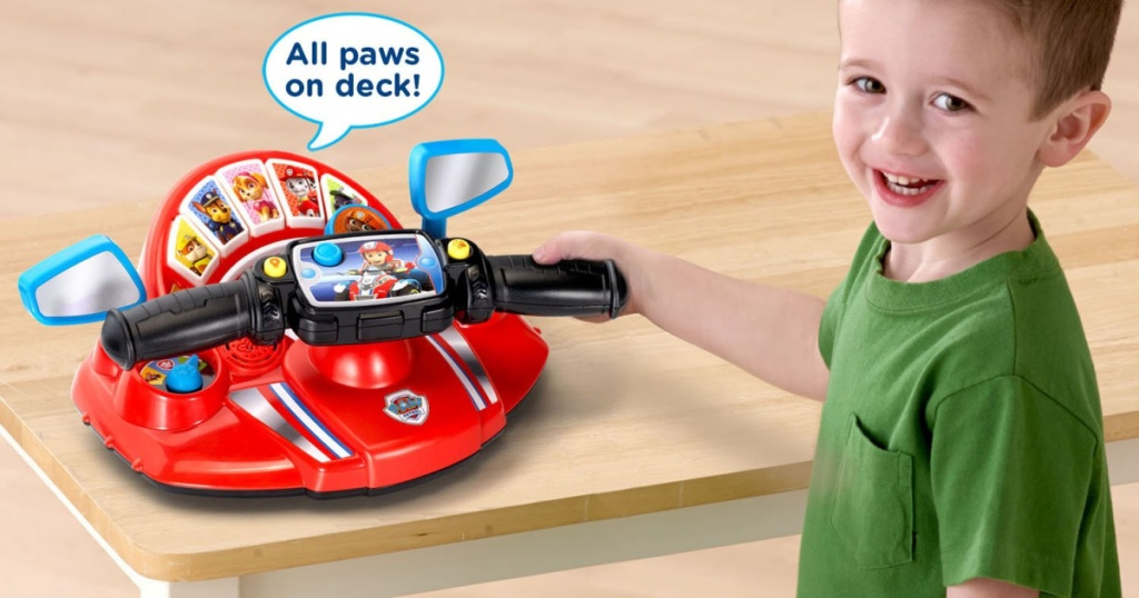 little boy playing with paw patrol driver toy