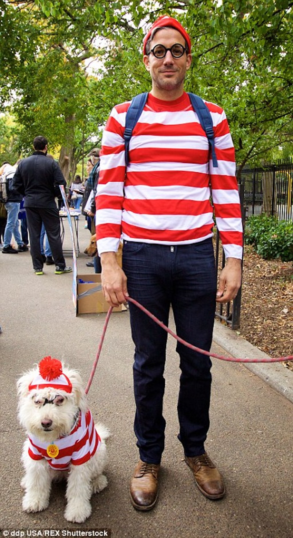 man and dog dressed up as where's waldo outside