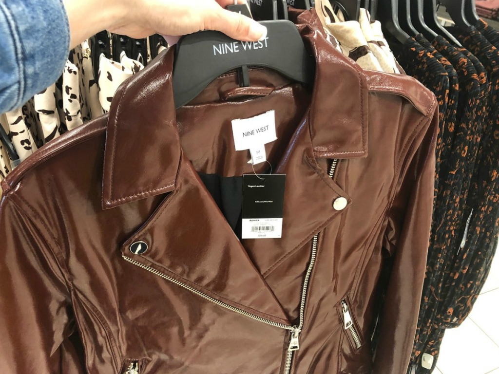 hand holding brown shiney jacket on hanger by store display
