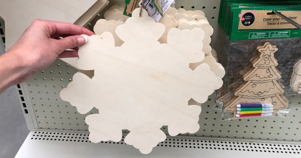 hand holding up wooden snowflake