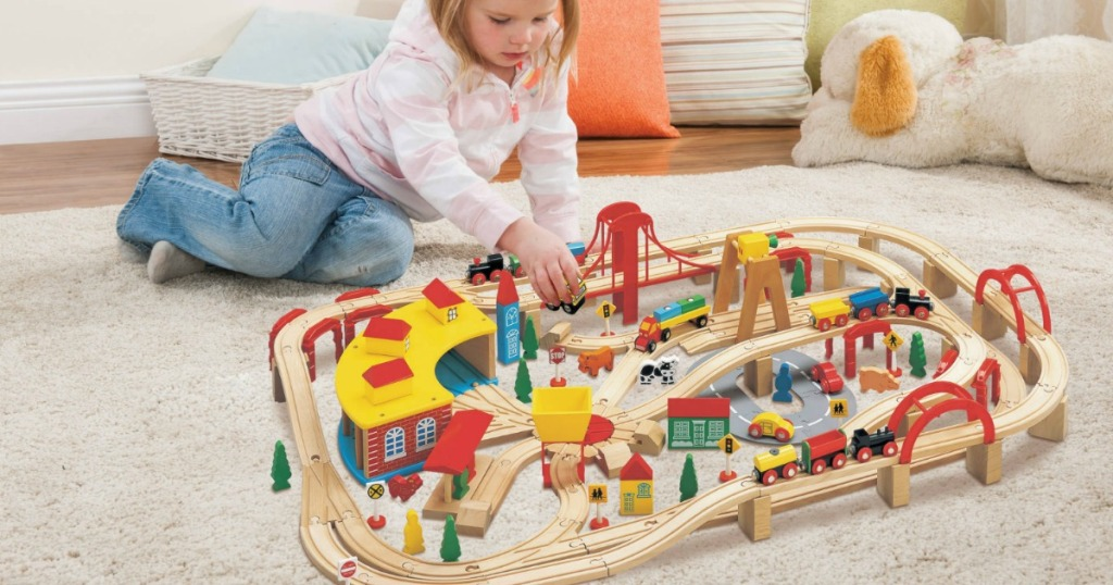 little girl playing with a train set