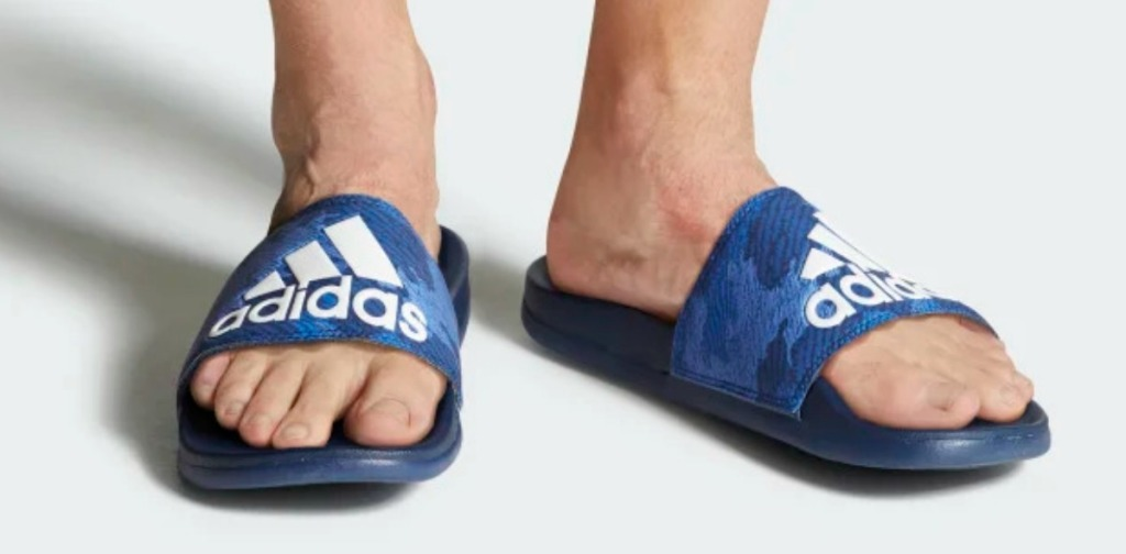 Men wearing blue printed slide sandals from adidas