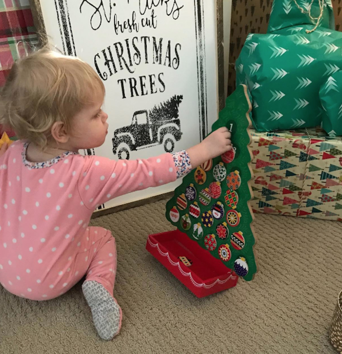 baby girl playing with advent tree countdown calendar