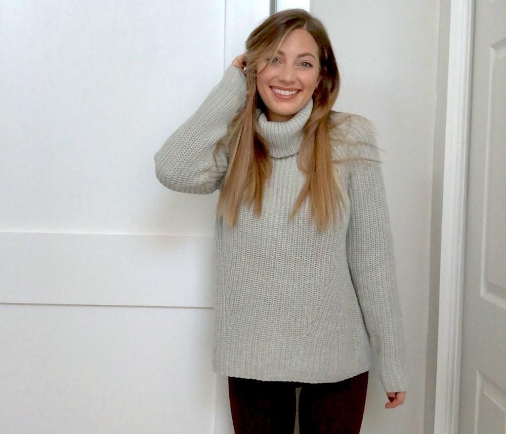 woman wearing gray turtleneck sweater smiling