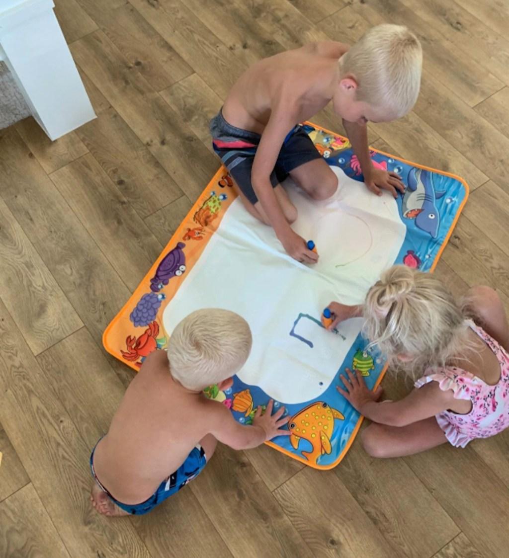 kids drawing on aquadoodle on mat on floor