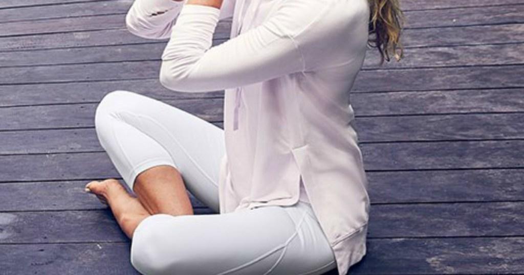 woman in white leggings doing a yogo pose