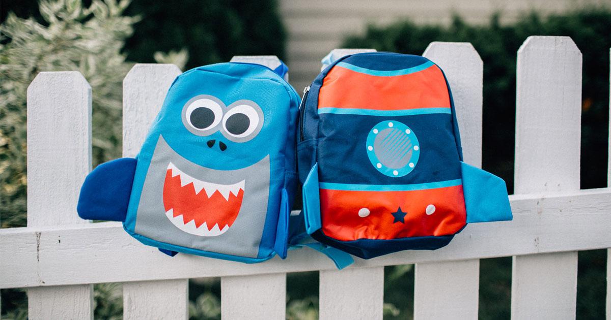 carried away little kids backpacks on a fence shark and rocket