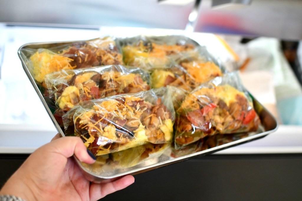 breakfast burrito pouches going into the freezer
