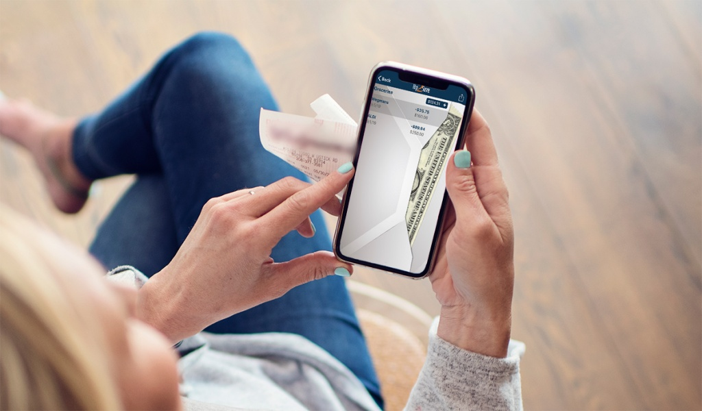 woman on smartphone using envelope budget