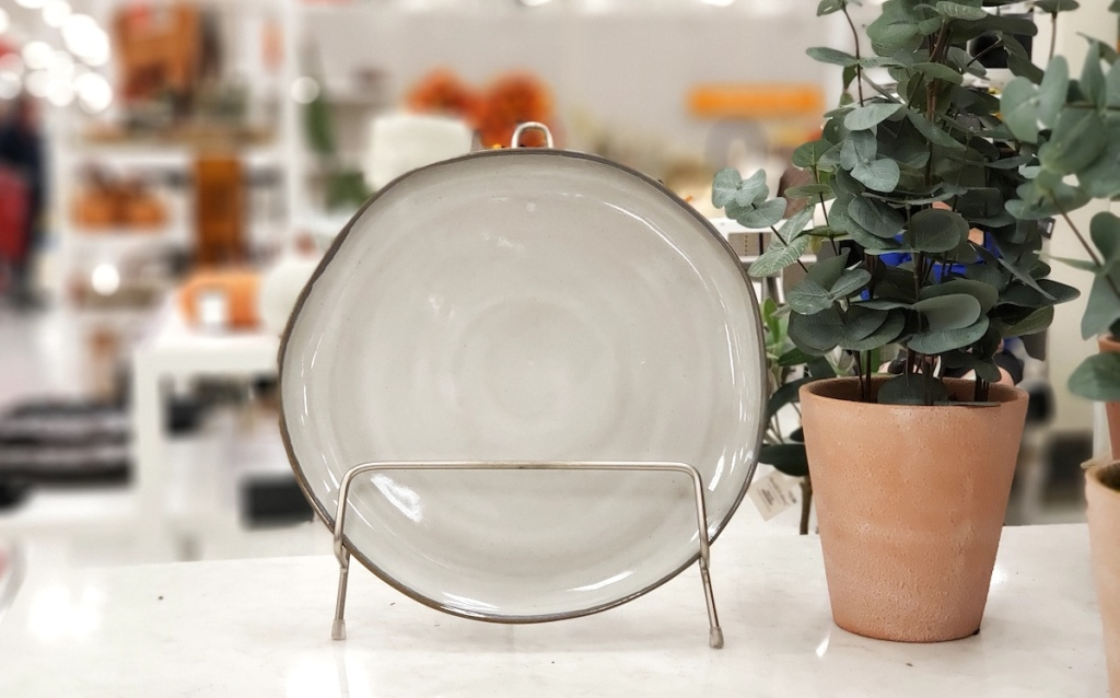 round dinner plate on stand next to faux plant