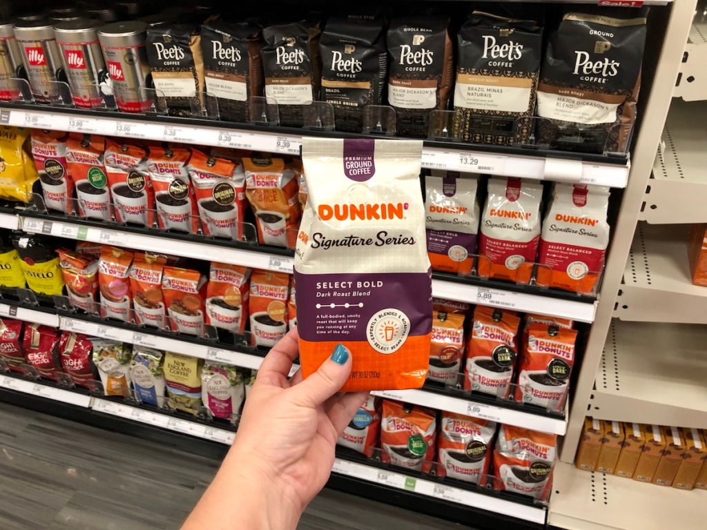 dunkin donuts signature series coffee bag held up in front of store shelf