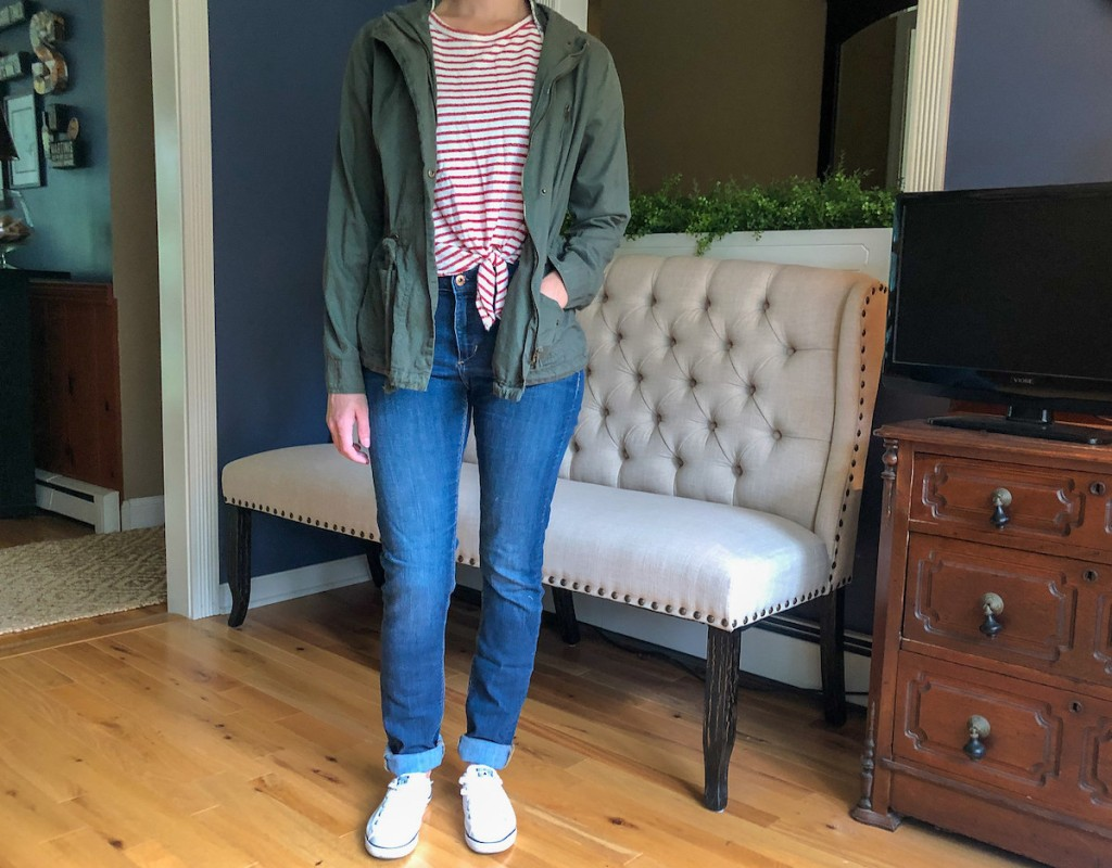 person wearing army jacket stripe shirt and jeans