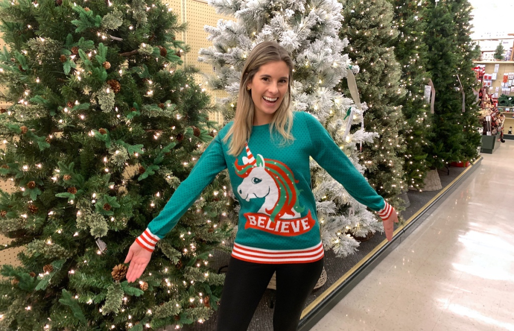 emily wearing ugly christmas sweater in store with christmas trees