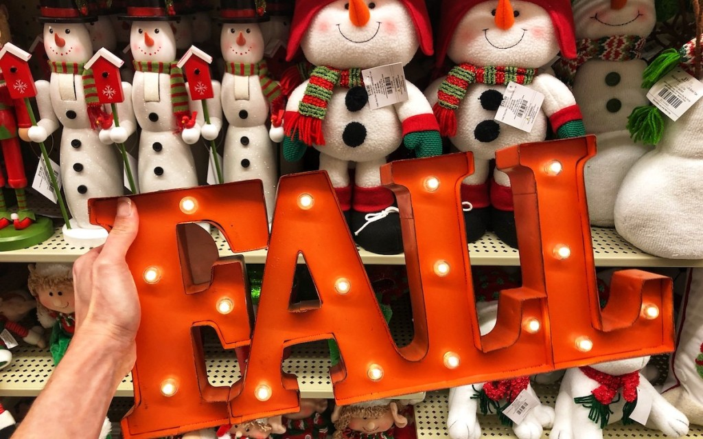 Fall light sign with snowmen on shelf in background