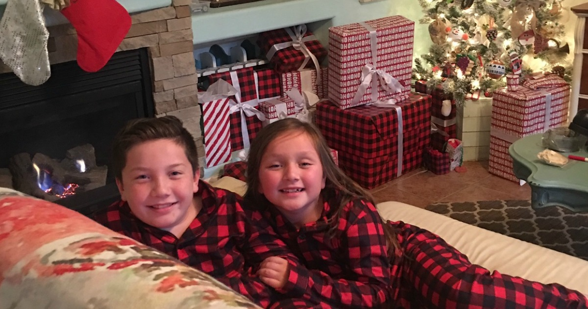 boy and girl sitting on couch with Christmas decor