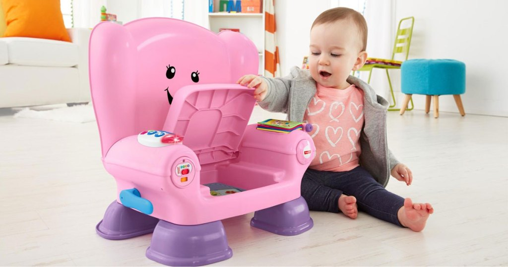 baby sitting in a room playing with the fisher-price laugh and learn pink chair