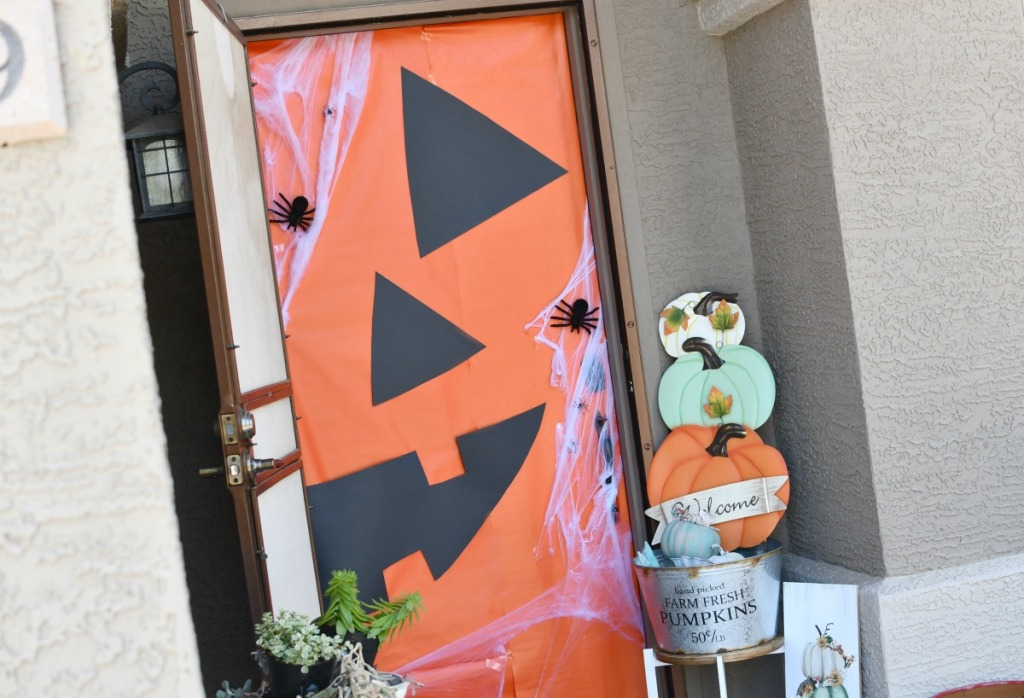 front door with jack-o-lantern wrapping paper on it