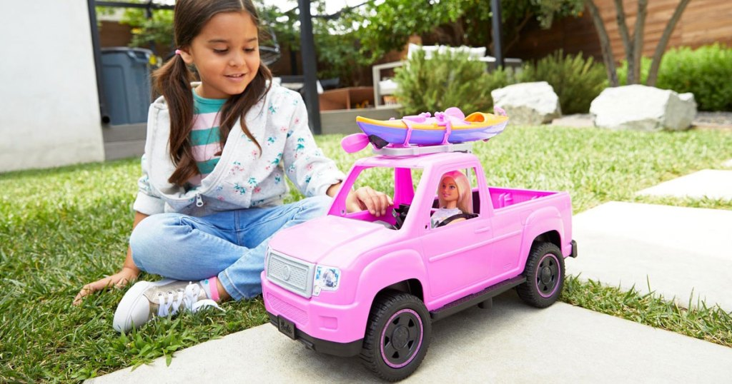 young girl playing with Barbie Kayak Adventure playset outside