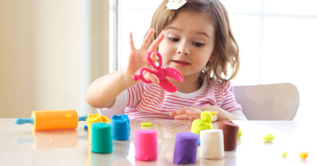 Little girl at a table playing with play-doh